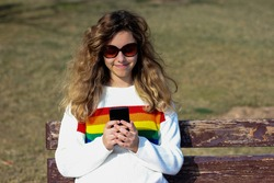 Pretty smiling teenager girl chating with online firends. Happy curly young girl wear rainbow sweater