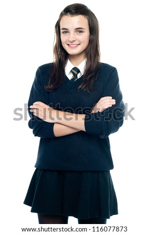 Pretty smiling teenager looking at you confidently. Arms folded