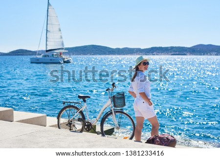 Pretty smiling tourist girl in white clothing and sunglasses standing at bicycle and backpack on paved stone sidewalk stairs on clear blue sea water, sailing cruse yacht and mountains background.