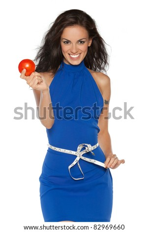 Pretty smiling woman in blue dress measuring waist with measurement type, holding a tomato, isolated on white - stock photo