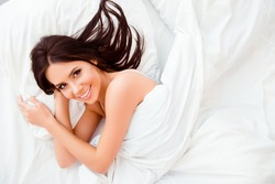 Pretty smiling woman lying in bed at morning