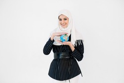 Pretty smiling young Arabic woman in hijab holding Earth globe planet in hands against white background. Earth day holiday concept.