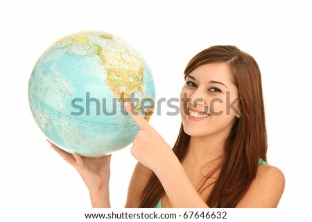Pretty smiling young lady holding a world globe and pointing to America