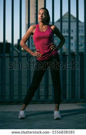 Pretty sporty lady in sporty clothes standing with hands on the waist and looking up
