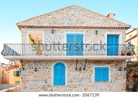 Pretty stone house with blue shutters and a balcony
