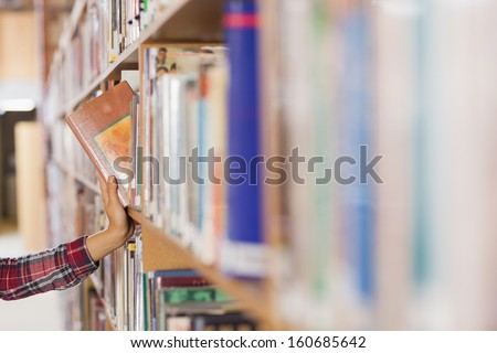 Pretty student taking book out of shelf in library