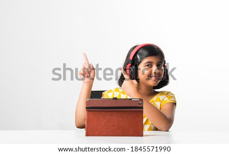 Pretty stylish Indian asian schoolgirl studying attending online lesson at home, social distance during quarantine, self-isolation, online education concept, home schooler