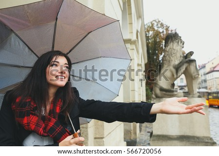 Pretty stylish woman in dark coat and red checkered scarf with umbrella. Romantic smiling woman in the city. #566720056
