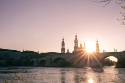 Pretty sunset through the towers of the Cathedral of The Pillar in Zaragoza, Spain, with the Stone Bridge over the Ebro river as foreground and a clear sky.