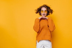 Pretty surprised lady in white pants fooling around in studio and jumping. Adorable girl in knitted sweater dancing on colorful background and touching chin with hands.