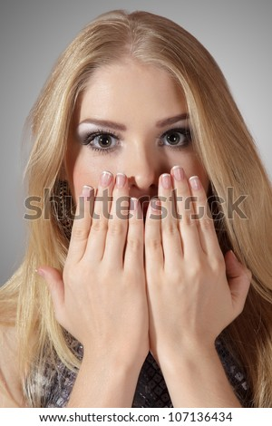 Pretty surprised woman with hands over mouth