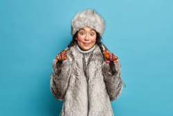 Pretty surprised young Asian woman holds pigtails dressed in outerwear isolated over blue background. Eskimo female wears hat and coat lives in arctic place. Winter time and clothes concept.