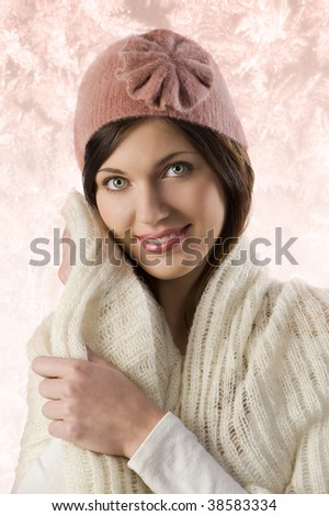 pretty sweet girl warming herself  with white scarf and a pink winter cap in a studio shot