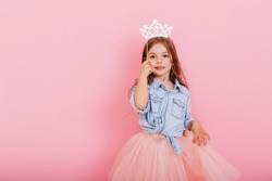 Pretty sweet little girl with long brunette hair in tulle skirt holding white crown on head isolated on pink background. Beautiful joyful child expressing true emotions. Place for text