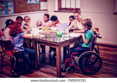 Pretty teacher helping pupils in classroom at the elementary school #700890781