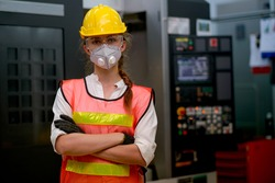 Pretty technician or worker or engineer woman with gray mask stand with confident action in workplace with concept collaboration during concern about public health of corona virus pandemic in people.