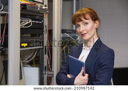 Pretty technician smiling at camera beside open server holding tablet pc in large data center
