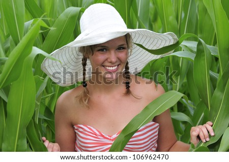 stock photo : pretty teen farm girl standing a a corn field