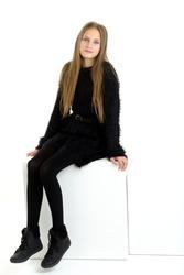 Pretty teen girl sitting on white cube in studio