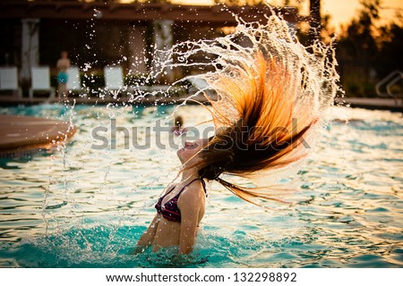 Pretty teen girl whipping her hair back in the pool and spraying water everywhere