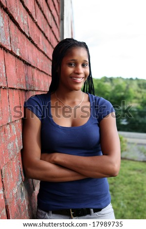 pretty teen standing against red weathered shingles - stock photo