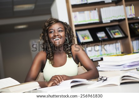 Pretty teenage black african college student girl studying and reading a book in college library #256961830