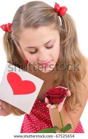 pretty teenage girl holding a valentine's card and looking at a rose isolated on white