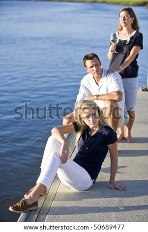 Pretty teenage girl relaxing on dock by water, parents behind