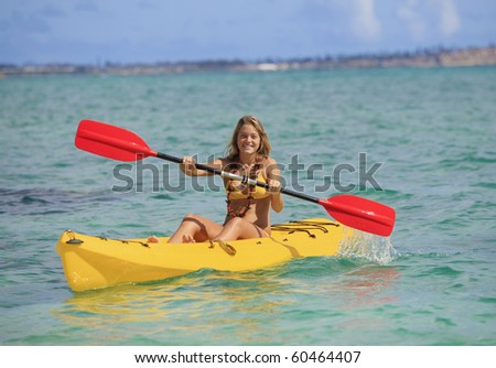 pretty teenage girl with her kayak paddling in the warm Pacific waters of Hawaii