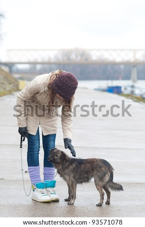 Pretty teenage girl with the dog on cloudy autumn day.