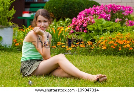 Pretty teenager girl sitting on the grass in the garden