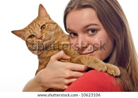 Pretty teenager model holding her pet, an orange striped tabby cat, looking smug