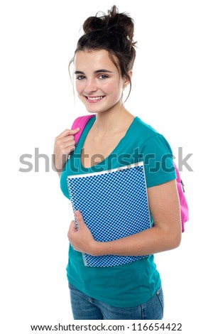 Pretty teenager ready to attend college. Carrying backpack on her shoulders