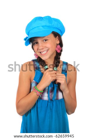Pretty ten year old adolescent multi ethnic girl with long dark hair on a white background wearing colorful blue hat