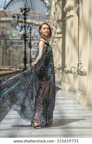 Pretty tender young model is walking in a short black dress with fashionable flutter transparent cape at old fashioned building with pillars