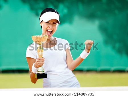 Pretty tennis player won the cup at the sport competition. Victory