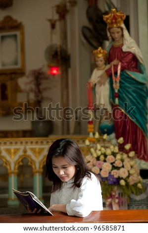 Pretty Thai woman study bible in Christian church .