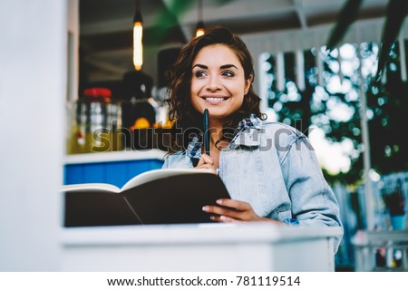 Pretty thoughtful brunette student thinking on creative ideas for creating new startup project sitting with notepad in coffee shop interior.Pensive female in good mood dreaming on developing work plan