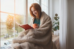 pretty thoughtful smiling young girl reading book and drinking morning coffee at home sitting next to the window wrapped in warm comfy blanket