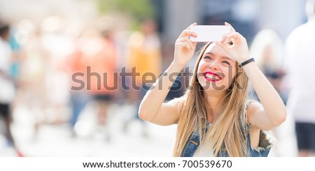 Pretty tourist teenager taking a photo with her mobile phone #700539670