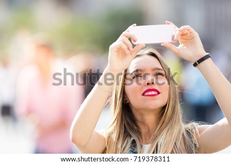 Pretty tourist teenager taking a photo with her mobile phone #719378311