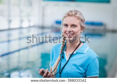 Pretty trainer holding a stopwatch at the pool Stockfoto ©