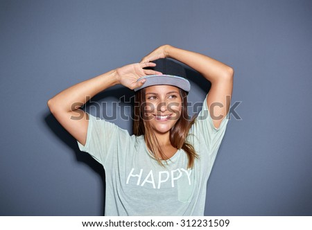 Pretty trendy young Asian student with a lovely friendly smile posing with her arms raised above her head in a baseball cap and t-shirt over a grey background, looking to the right