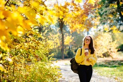 Pretty university student girl drinking coffee from disposable cup in a autumn park, adult schoolgirl enjoying education, female wearing with yellow sweater, scarf and glasses, back to school