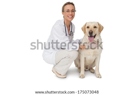 Pretty vet petting yellow labrador dog smiling at camera on white background