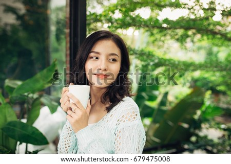 Pretty vietnamese woman enjoying her morning coffee on a veranda