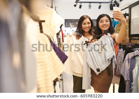 Pretty Vietnamese young women taking selfie in clothing shop