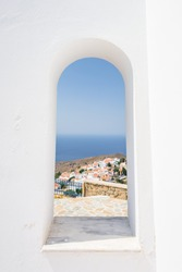 Pretty view from a window of the Holy white blue church of agios theologos above the village Nikia over the greek sea on the edge of a volcano on the island of Nisyros, Kos, Dodecanese, Greece