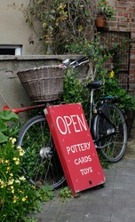 Pretty village shop sign attached to a Dutch bicycle with basket