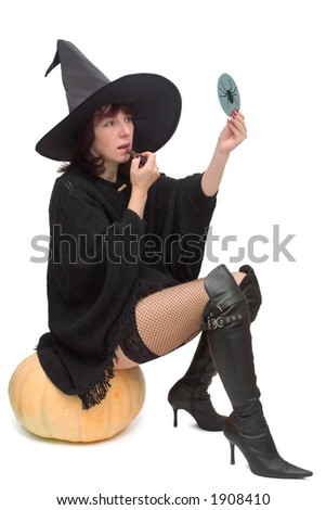 Pretty witch sitting on large pumpkin and making up to prepare for Halloween